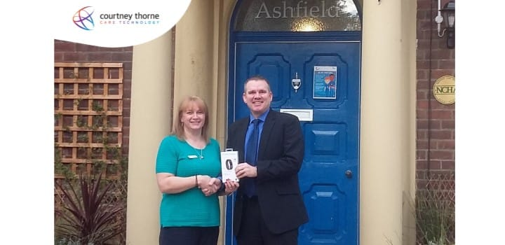 Courtney-Thorne-handing-over-fitbit-prize-from-let-loose-draw-to-winner-in-front-of-care-home-shaking-hands